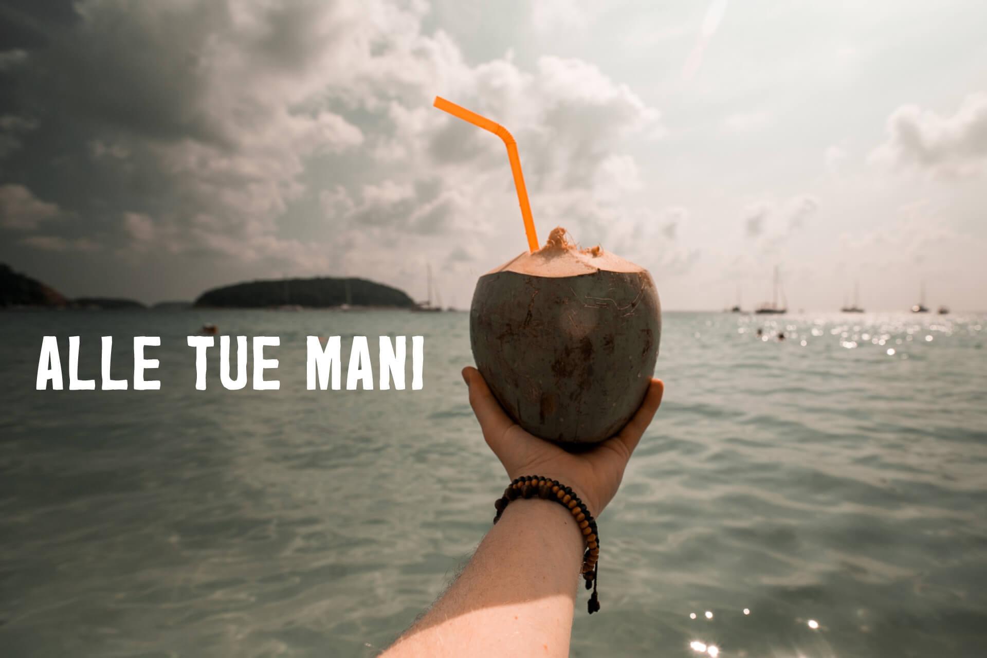 Uomo in barca tiene cocco verde con cannuccia arancione