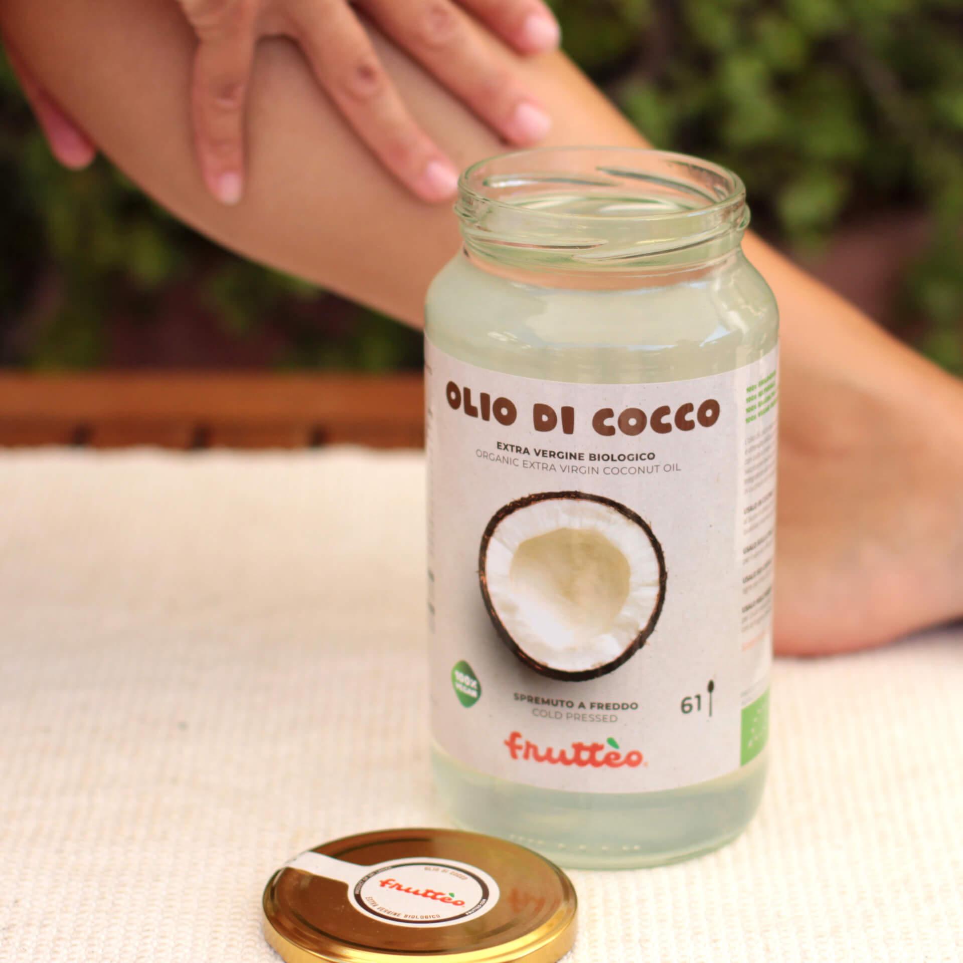 Barattolo Olio di Cocco Frutteo da 1000 (mille) millilitri aperto - con mani che spalmano su polpaccio