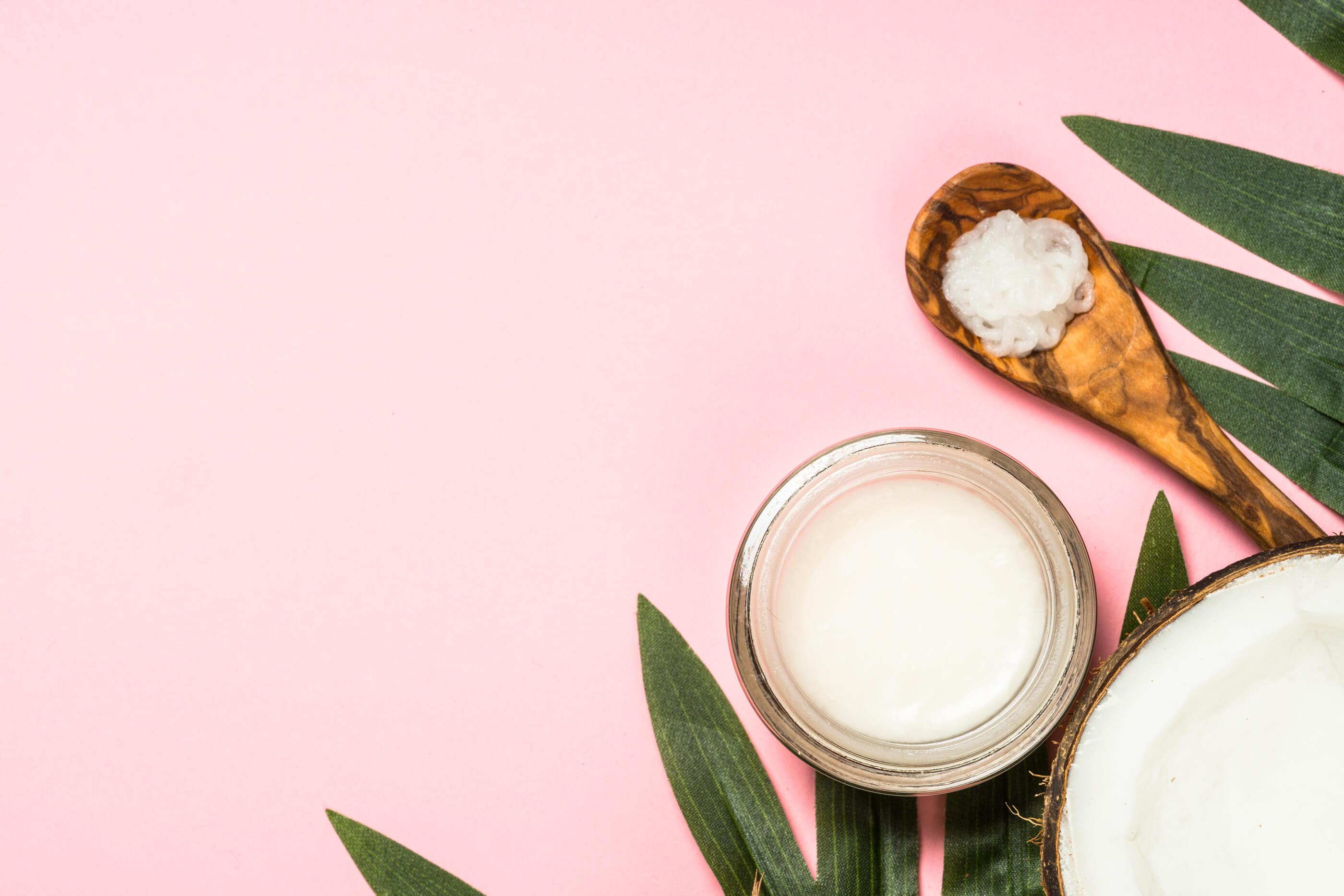Foto con barattolo di olio di cocco e cucchiaio in legno visti dall'alto su piano di colore rosa